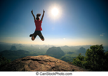 passionate successful young woman jumping on mountain peak