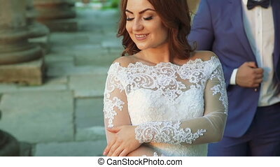 Passionate wedding couple stands in pose near the castle....