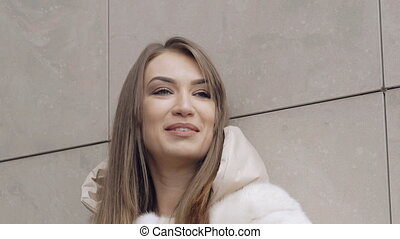 Passionate woman in furry coat smiling in front of camera....