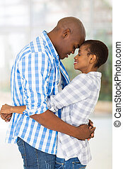 young african couple hugging with eyes closed