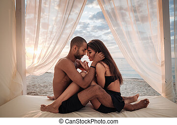Passionate young couple sitting on the beach - Passionate...