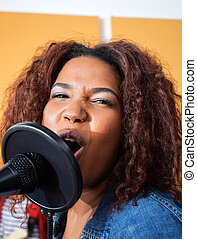 Passionate Young Woman Singing In Recording Studio