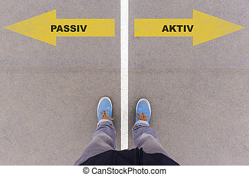 Passiv / Aktiv (German for passive and active ) direction sign text on asphalt ground, feet and shoes on floor, personal perspective footsie concept