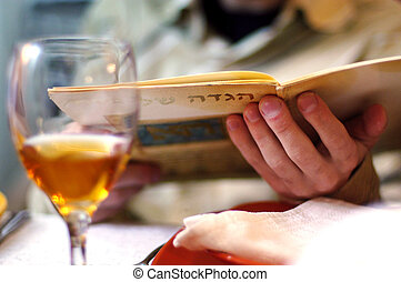 Passover Dinner - Man reads in the Haggadah book during...