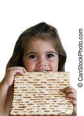 Jewish girl eating a matzo in passover Jewsih holiday.
