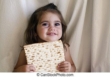 Passover Jewish Holiday - Jewish girl eating a matzo in...
