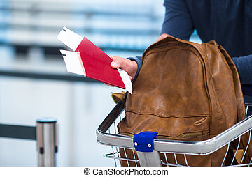 Passport and boarding ticket and a backpack in the luggage trolleys
