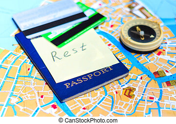 Passport, credit cards and compass on a map