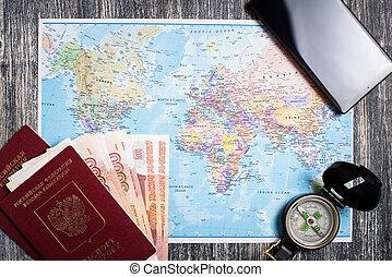 Passport, money, compass and camera on map