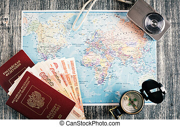 Passport, money, compass and camera on map