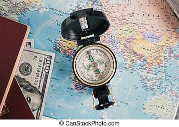 Passport, money, compass on map