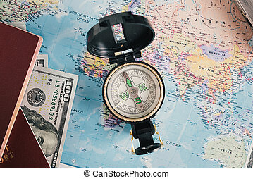 Passport, money, compass on map