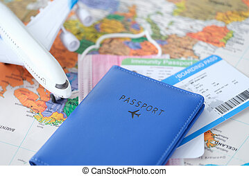 Passport with toy plane tickets and covid vaccination certificate are on world map