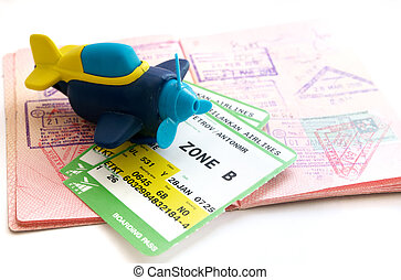 Passport with visas, toy airplane and boarding pass.