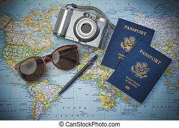 Passports for travel, camera and glasses on a map of the world