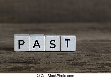 Past, written in cubes on a wooden background