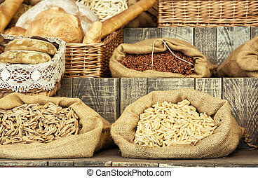 Pasta and pastries in bags on the wooden retro board