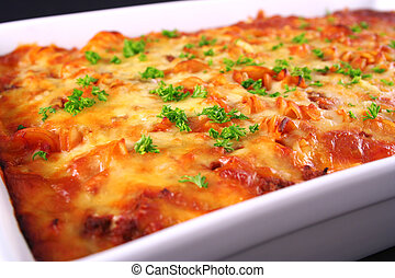 A tray of colorful freshly cooked pasta bake with parsley garnish straight from the oven shot an an angle