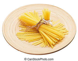 Pasta bunch composition on a wooden plate, isolated on white