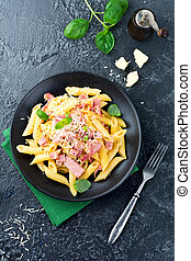 Pasta carbonara with prosciutto and parmesan cheese on black background. Top view.Selectiv focuse.