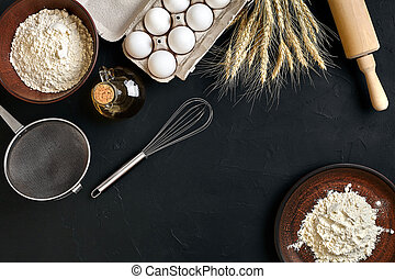 Pasta cooking ingredients on black kitchen table. Top view with space for your text