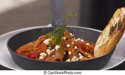 Pasta dish with tomato sauce and bread on the side