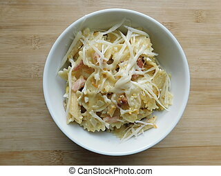 pasta farfalle with mushrooms, cheese and bacon in a white plate on a wooden table.
