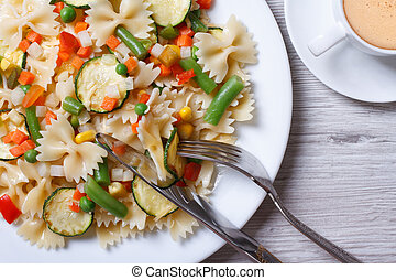 pasta farfalle with vegetables and coffee top view closeup