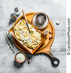 Pasta fettuccine in a bowl with garlic, thyme and sauce in bowl.