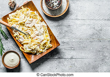Pasta fettuccine on a plate and sauce in a bowl.