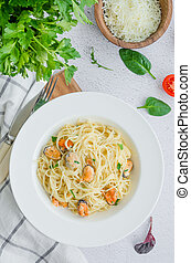 Pasta in a creamy sauce with mussels, cheese, garlic and parsley on a white plate on a light stone background. Rustic style. Vertical orientation. top view