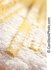 Close-up of pasta (mafaldi) in flour. Selective focus on foreground.