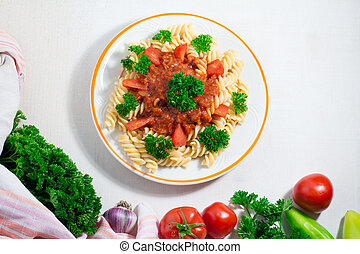 pasta in tomato sauce with tomatoes decorated with parsley on a white wooden table.