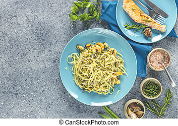 Pasta linguine with mushrooms, shrimps and seafood mussels, cheese and herbs, in blue ceramic plate on a light gray surface.