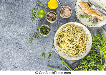 Pasta linguine with mushrooms, shrimps and seafood mussels, cheese and herbs, in ceramic plate on a light gray surface.