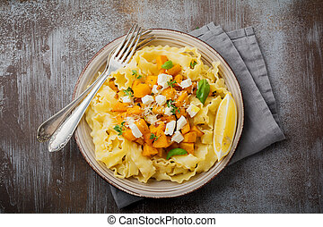 Pasta Mafaldine Napoletane with baked pumpkin, feta cheese and seasoning herbs in ceramic plate on gray concrete old background. Selective focus. Rustic style. Top view.