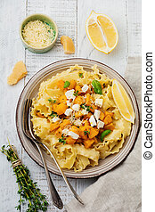 Pasta Mafaldine Napoletane with baked pumpkin, feta cheese and seasoning herbs in ceramic plate on white wooden background. Selective focus. Rustic style. Top view.
