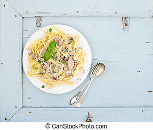 Pasta mafaldine with mushrooms and cream sauce in white ceramic plate over light blue wooden background. Top view. Copy space