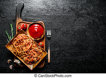 Pasta on a wooden plate with tomato sauce in bowl and rosemary.