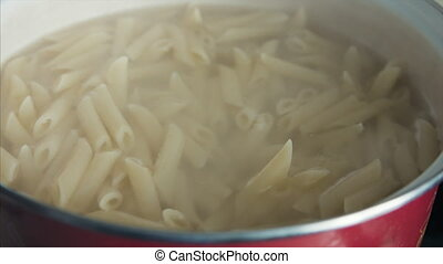 Pasta (penne) in boiling water, close up