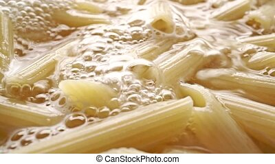 Pasta penne in boiling water, close up dolly shot