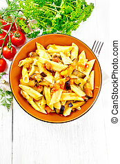 Pasta penne with eggplant and tomatoes on board top