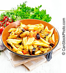 Pasta penne with eggplant and tomatoes on light board