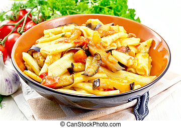 Pasta penne with eggplant and tomatoes on table