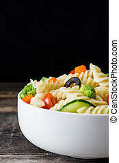Pasta salad in bowl with vegetables