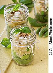 Pasta salad in jars with farfalle, salad greens, peas and feta