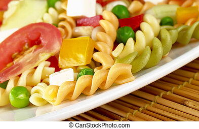 Pasta salad with fresh vegetables (tomato, pea, bell pepper) and cheese (Selective Focus, Focus on the first pasta)