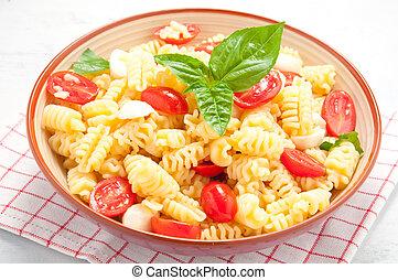 Pasta salad with tomatoes, olives, mozzarella and basil