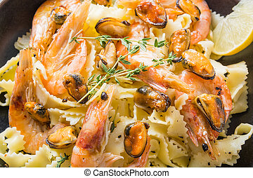 Pasta Mafaldine or reginette with seafood, shrimps, mussels, close up. Traditional dish in Italy.