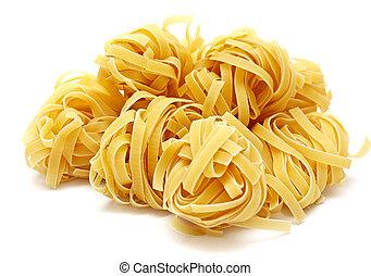 Pasta tagliatelle - Nests of dry pasta tagliatelle on white ...